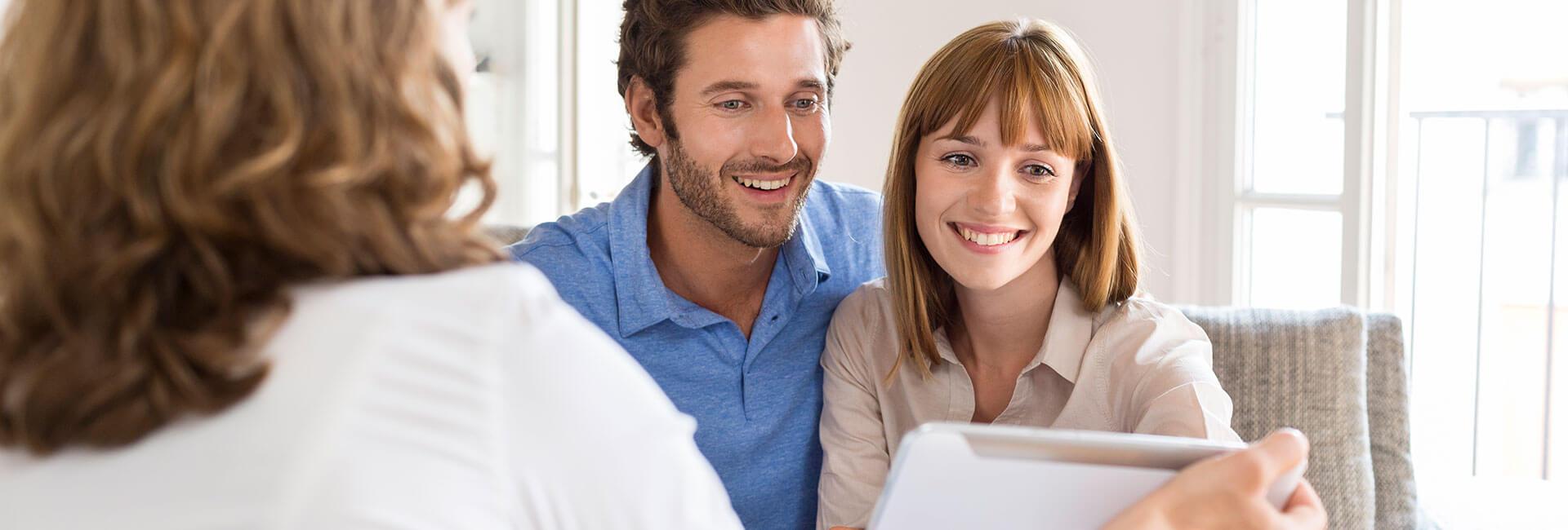 Günstiger Zahnersatz von ReDentes bringt ein Paar im Gespräch mit der Zahnärztin zum lächeln