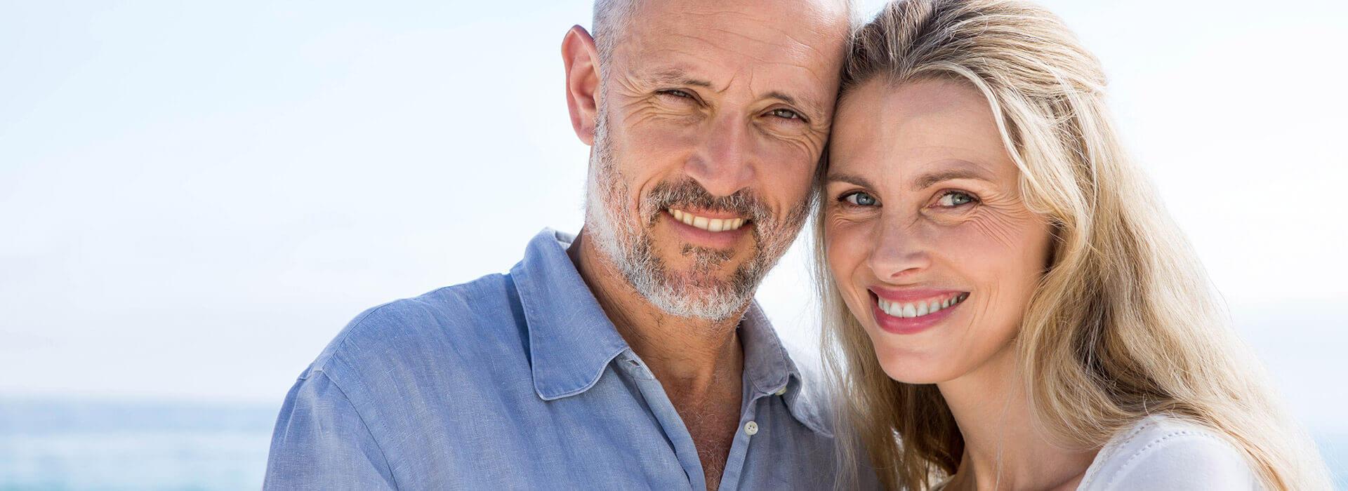 Zufriedenes strahlendes Paar mit professionellen Zahnersatz von ReDentes