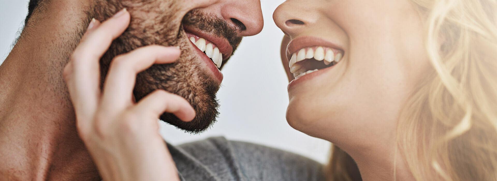 Überglückliches Paar strahlt wegen des günstigen und professionellen Zahnersatzes von ReDentes